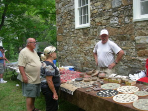 Dennis Zeiders [right] shows off some of his pottery and a plow to visitors at the Tuscarora Academy. He, his cousin Steve and Andy all have different items which makes a full-rounded display of items that describes how the American Indians lived and maintained their way of life.