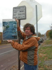 Author David DeKok shows a photo of what the street behind him used to look like, before residents in Centralia, PA, relocated and houses were torn down. Photo by Sheila McCarthy Yorks.